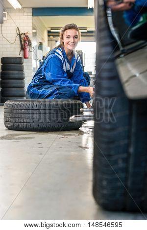 Portrait of happy female mechanic changing car tire at automobile shop