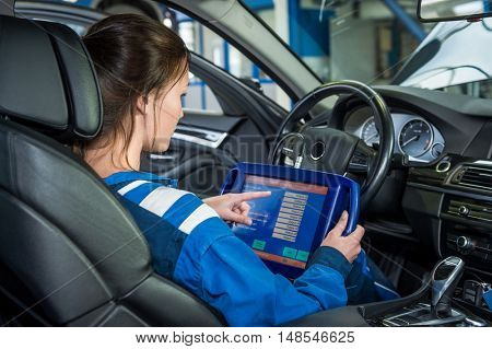 Side view of young female mechanics using tablet computer in car at garage