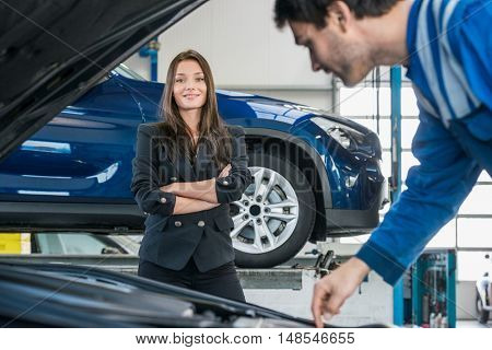 Portrait of confident young businesswoman with mechanic repairing her car in foreground at garage