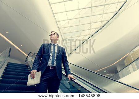 Businessman Walking Down Escalator Concept