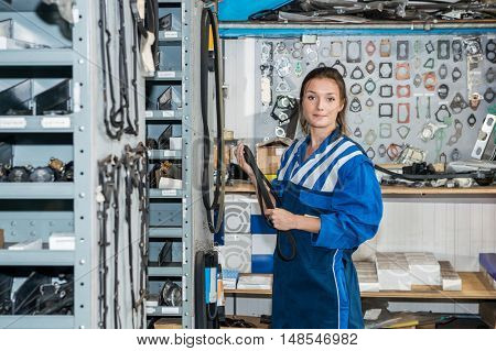 Portrait of young female mechanic holding timing belt in warehouse of garage