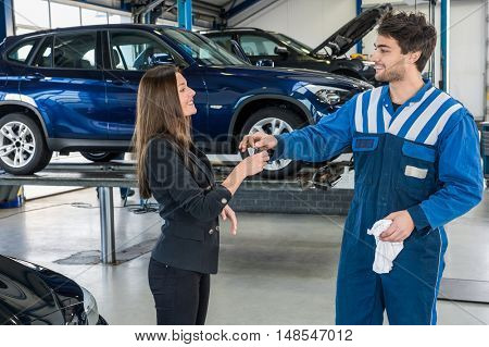 Happy young businesswoman receiving car key from mechanic after servicing at garage
