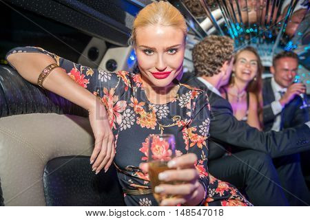 Portrait Of Beautiful Young Woman With Champagne Flute In Limo