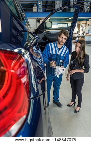 Young male mechanic preparing checklist while standing with customer by car in garage