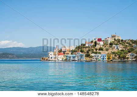 View over bay of Kastelorizo on sunny summer day. Island coast with typical colorful Greek houses and clear turquoise sea water. Dodecanese, Greece