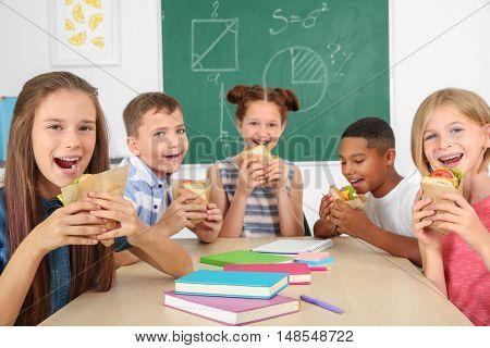 Schoolchildren having lunch in classroom