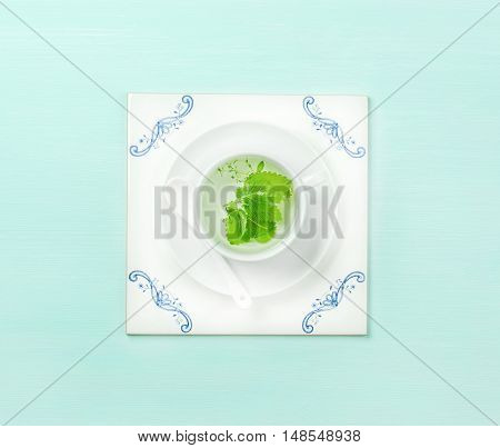 Cup of herbal tea on white ceramic tile board over mint pastel background. Top view