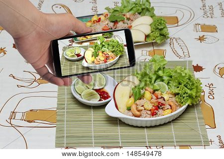 Using mobile phone to take photo a dish of Fried rice with mixed vegetable for share to social network. Selective focus.