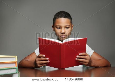 African American boy reading book on grey background