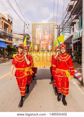 Phuket Thailand - Aug 26 2016 : Unidentified men loading Thai King and Queen picture as leader of parade of various schools in Phuket province on opening ceremony of yearly provincial sport.