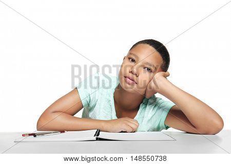 African American boy making homework on light background