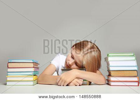 Cute girl sleeping on books on grey background