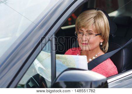 Portrait of attractive well-dressed senior woman sitting in a car and looking road map