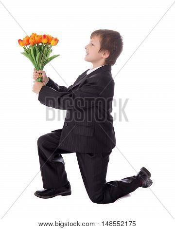 Little Boy In Business Suit Giving Flowers To Somebody Isolated On White