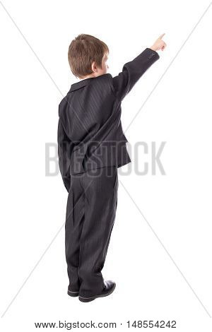 Back View Of Little Boy In Business Suit Pointing At Something Isolated On White