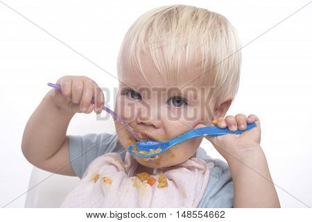 Cute young boy feeding himself with messy face white background