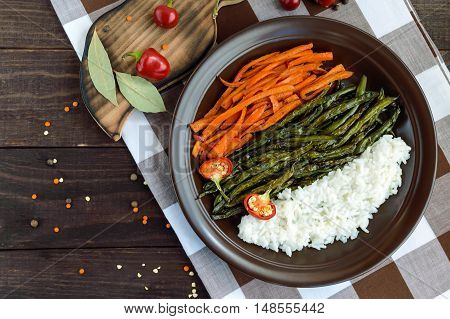 Baked vegetables (asparagus beans and carrot) boiled rice and rye croutons. Vegetarian cuisine. The top view