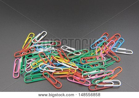 Colorful Paper clips isolated on black background.
