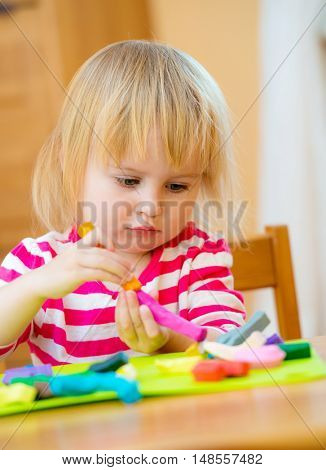 lovely little girl sitting at the table engaged in modeling plasticine