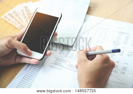 Man working at office holding a pen with documents Account book report and Using smart phone on his desk.