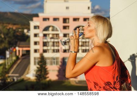 Beautiful woman standing on balcony in luxury hotel in Bulgaria at sunset and drinking wine.