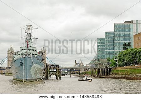 LONDON UK - JULY 8 2016: HMS Belfast (Royal Navy light cruise) - a warship Museum with Tower bridge at the back. Belfast moored in London on River Thames and operated by the Imperial War Museum.