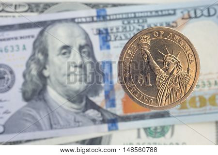 One dollar coin over one hundred dollar notes
