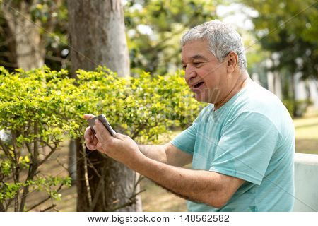 Senior man typing message on smart phone in the park