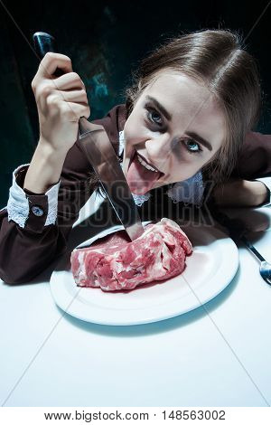 Portrait of a young girl with knife and and a piece of raw meat on a plate. Girl in school uniform as killer. The image in the style of Halloween and Addams family