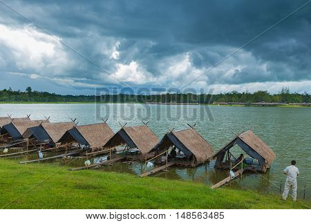 View of Huay Tung Tao Lake with food rafts around the lake with mountains and dark blue thunder storm clouds in the background