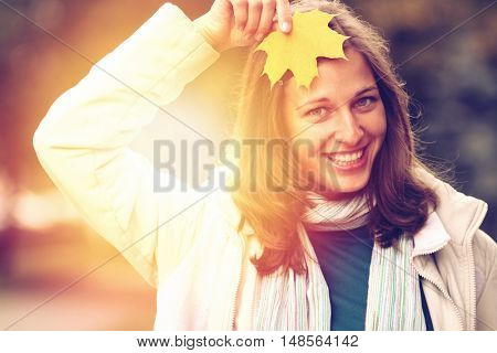 young beautiful woman with a bouquet of maple leaves