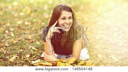 woman calling by phone in autumn park