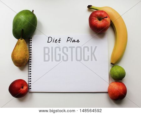 Diet plan on notebook paper page with empty copy space and colorful organic fresh fruits apple banana pear peach mango isolated on white table background Diet fitness healthy eating food nutrition lifestyle concept