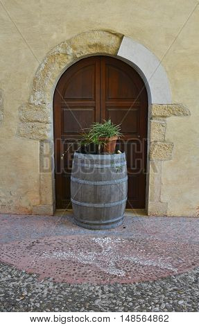 A wooden barrel outside an old wooden door in the small north east Italian town of Valvasone in Friuli Venezia Giulia