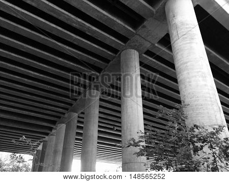 Black and white shot underneath a highway overpass.