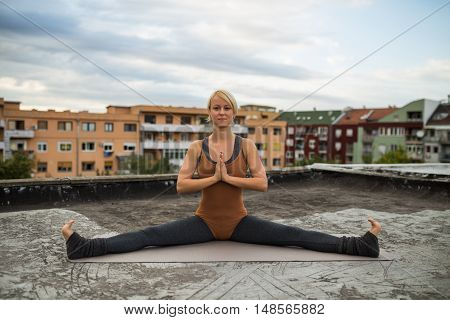 Beautiful woman is practicing yoga on the roof.
