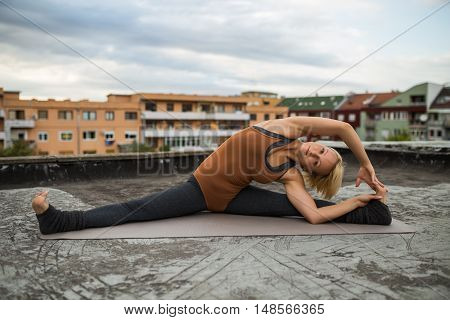 Beautiful woman practicing yoga on the roof,Parivrtta Janu Sirsasana/Revolved Head-to-Knee Pose