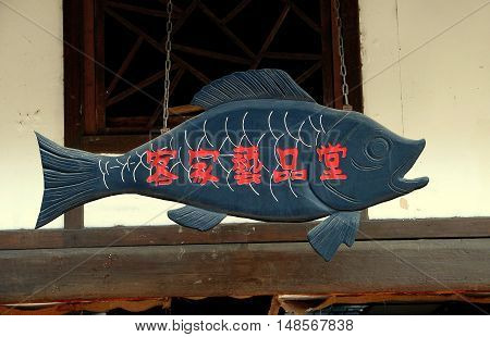 Luo Dai China - October 13 2007: A large wooden symbolic fish with Chinese characters hangs on chains in front of a Hakka home