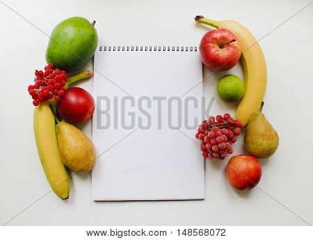 Notebook planner with blank empty page and colorful organic fresh fruits apple banana pear peach mango berries isolated on white table background Diet fitness planning, healthy eating food nutrition lifestyle concept with copy space close up