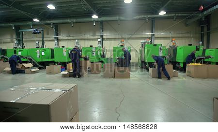 LUBLIN, POLAND - JUN 2016: Workers Operate Equipment Manufacture of Plastic Parts.