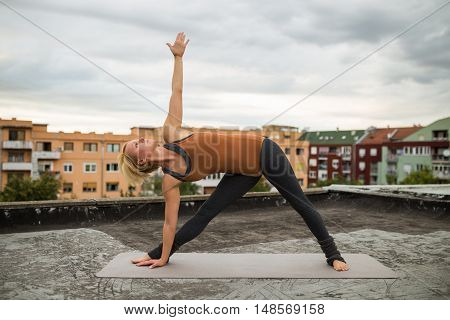 Beautiful woman practicing yoga on the roof,Trikonasana right/Right triangle pose