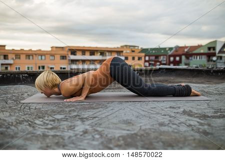 Woman practicing yoga on the roof,Ashtanga Namaskara/Knees, Chest and Chin pose