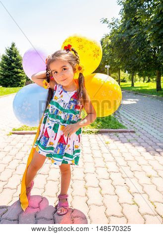 Adorable little child girl with balloons on summer nature background.