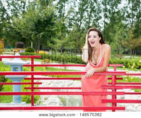 Portrait of the young beautiful smiling woman with long hair outdoors