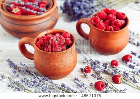 pottery with berries and lavender on wooden table