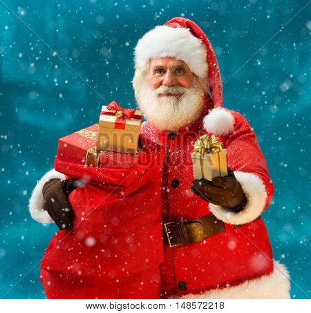 Smiling Santa Claus with new year presents and looking at camera. Merry Christmas & New Year's Eve concept. Close up on blurred blue background.