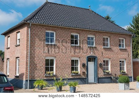 red brick house with white windows and white entrance