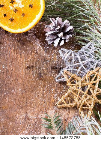 Christmas background with orange cloves stars and fir branches on wooden background