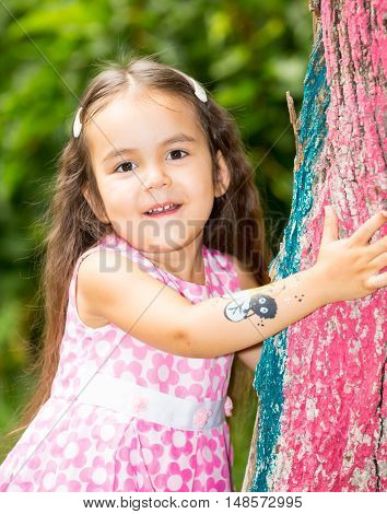 Adorable little child girl on summer green nature background.