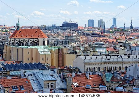 Aerial view of the traditional red roofs of the city of Prague Czech Republic with the church of St Virgin Mary of the snow on the left and skyscrapers of Pankrac district in the distance.
